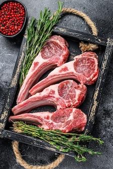 Côtelettes de viande d'agneau crues steaks dans un plateau en bois