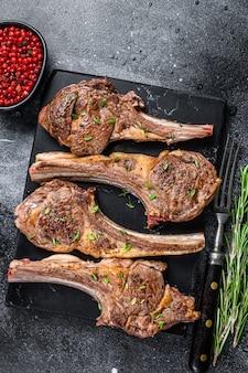 Côtelettes de viande d'agneau frites au barbecue sur une planche de marbre. fond noir. vue de dessus.