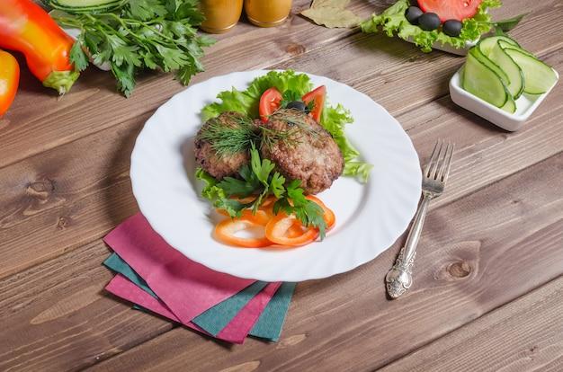 Côtelettes de viande frites avec des légumes et des herbes sur un fond en bois foncé
