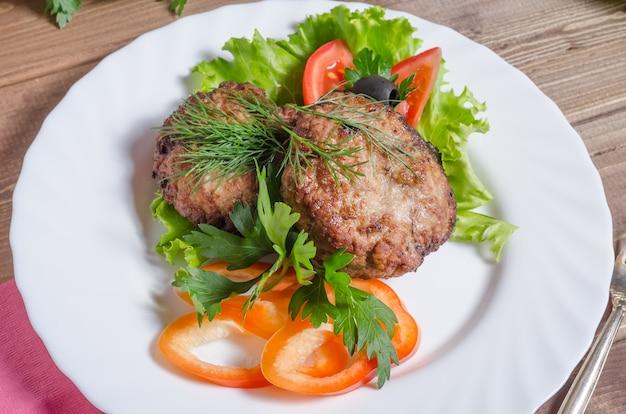 Côtelettes de viande frites avec légumes et herbes sur un gros plan de plaque blanche