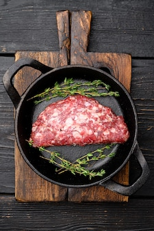 Côtelettes de viande hachée crue. steak de boeuf haché frais ensemble de hamburgers, dans une poêle en fonte, sur fond de table en bois noir, vue de dessus à plat