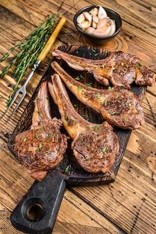 Côtelettes de viande de mouton d'agneau grillé sur une planche à découper