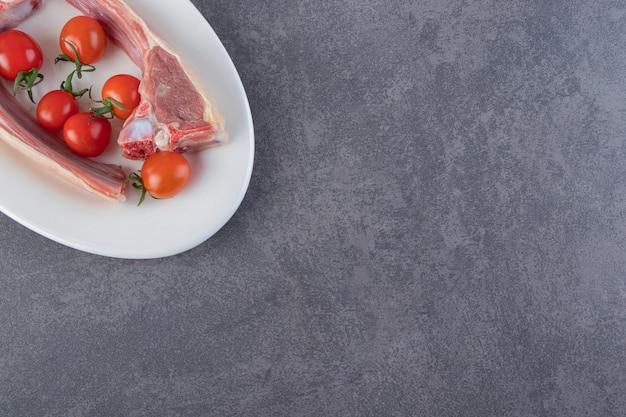 Côtelettes de viande non cuites aux tomates cerises sur table en pierre.