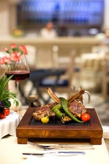 Côtes d'agneau brochette et légumes grillés servis sur un plateau carré