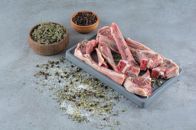 Côtes d'agneau crues aux herbes et grains de poivre placés sur une table en pierre.