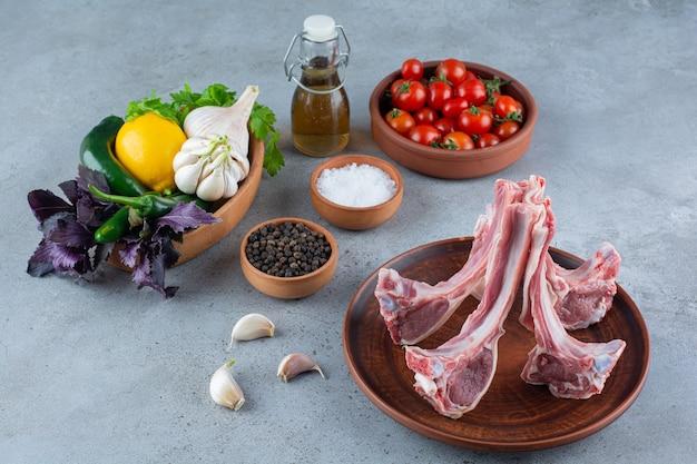 Côtes d'agneau crues aux légumes et épices placés sur une table en pierre.