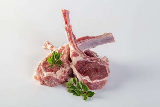 Côtes d'agneau crues fraîches sur fond blanc