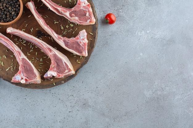 Côtes d'agneau crues placées sur une table en pierre.