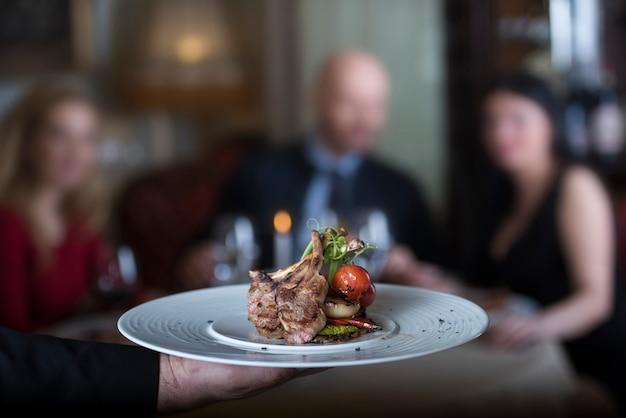 Côtes d'agneau grillées délicieuses, servies avec grillades de tomates et décorées de radis