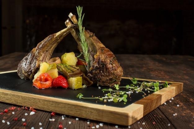 Côtes d'agneau grillées sur une planche à découper avec des légumes grillés.