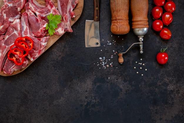 Côtes et assaisonnements de viande d'agneau fraîche crue sur une surface sombre