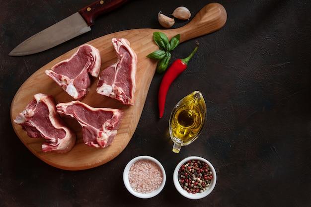Côtes et assaisonnements de viande d'agneau frais crus sur une planche à découper en bois. vue de dessus, gros plan sur fond sombre