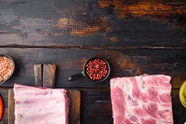 Côtes crues avec un ensemble de romarin et de légumes, sur une vieille table en bois foncé