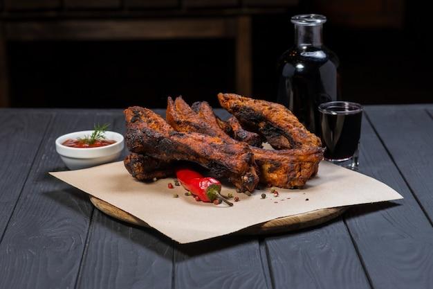 Côtes frites avec du poivre et une bouteille de vin sur une surface en bois noir