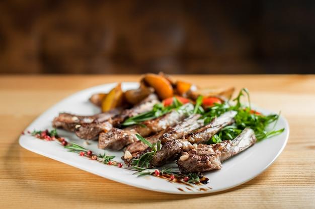 Côtes grillées juteuses, cuites avec des légumes et du romarin