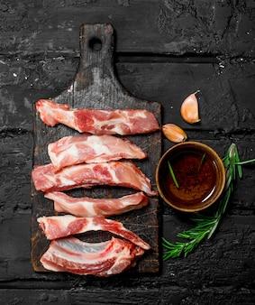Côtes levées crues avec sauce tomate et épices. sur une surface rustique noire.