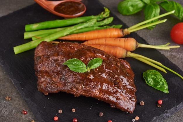Côtes levées de porc rôties et grillées d'un barbecue d'été servies avec légumes, asperges, carottes miniatures, tomates fraîches et épices. côtes fumées sur la surface de la pierre noire. vue de dessus,