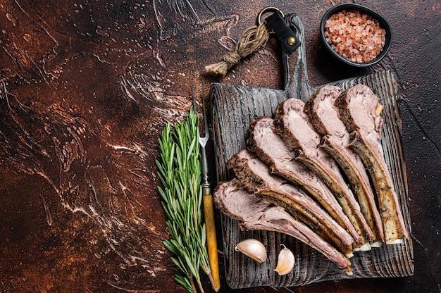 Côtes de mouton d'agneau grillé côtelettes de biftecks sur planche de bois