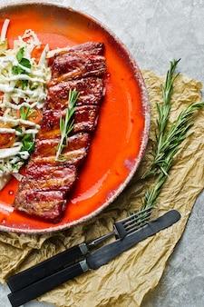 Côtes de porc au barbecue avec accompagnement de salade verte.