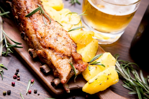 Côtes de porc au four avec pommes de terre, romarin et verre de bière