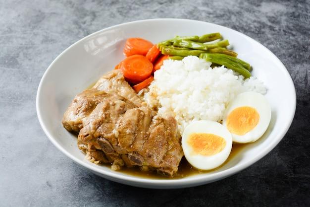 Côtes de porc au four avec riz, œuf à la coque et légumes