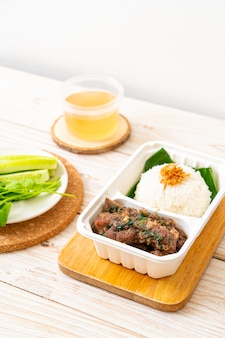 Côtes de porc au four avec sauce et riz en boîte de livraison