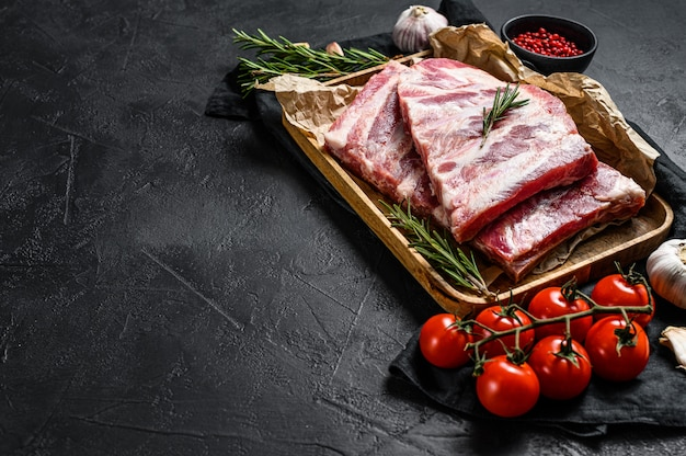 Côtes de porc cru frais au romarin et à l'ail dans un bol en bois. fond noir. vue de dessus. espace pour le texte