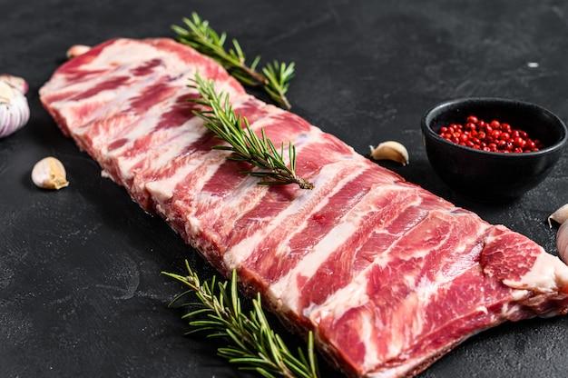 Côtes de porc cru frais au romarin et à l'ail. mur noir. vue de dessus