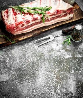 Côtes de porc crues aux herbes et épices. sur fond rustique.