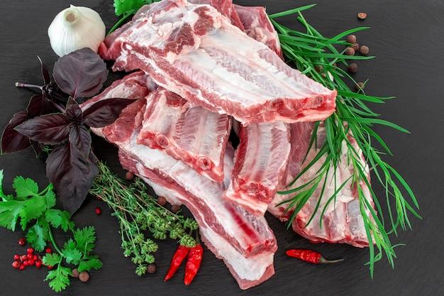Côtes de porc crues et condiments disposés sur une planche à découper en pierre noire.