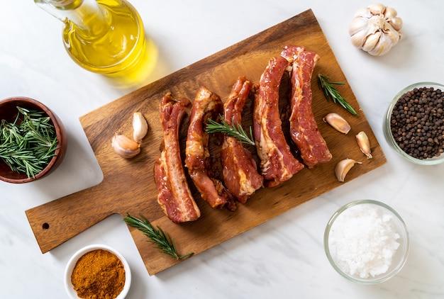 Côtes de porc crues fraîches prêtes à rôtir avec des ingrédients