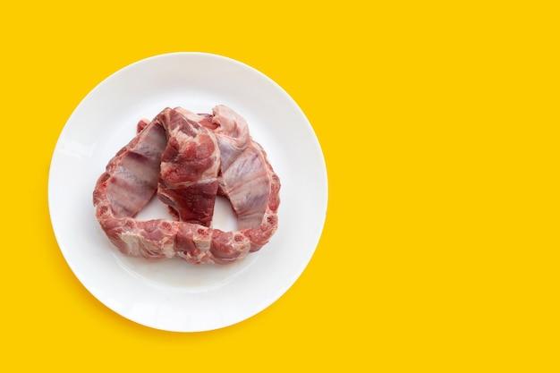Côtes de porc crues en plaque blanche sur fond jaune.