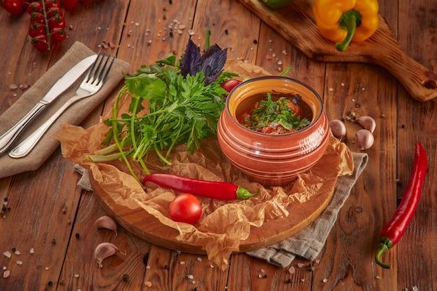 Côtes de porc cuites, pommes de terre, aubergines et poivrons, fond en bois