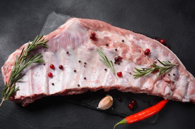 Côtes de porc entières crues. viande de porc fraîche et ingrédients : épices, sel et romarin sur fond sombre