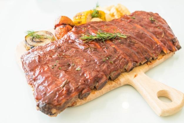 Côtes de porc grillé avec sauce barbecue et légumes et frites sur planche à découper en bois