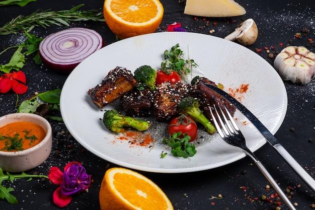 Côtes de porc grillées au miel avec tomates et brocoli sur une surface sombre