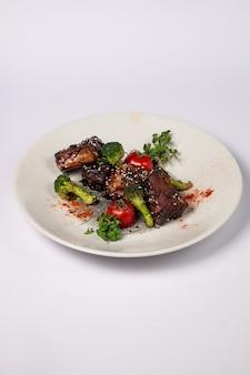 Côtes de porc grillées au miel avec des tomates et du brocoli sur une surface blanche