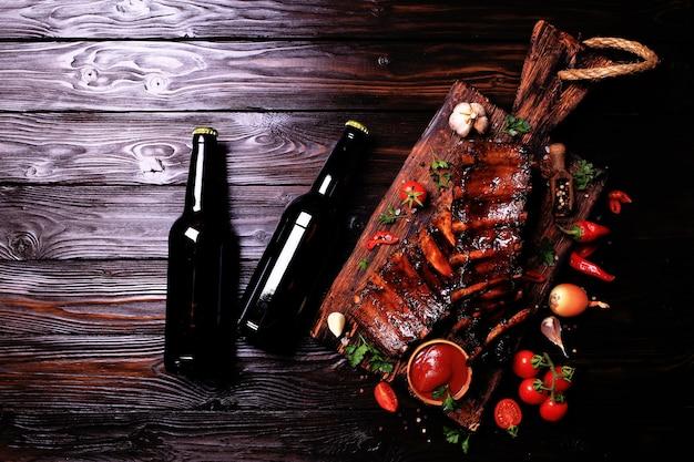 Côtes de porc grillées avec des épices à la bière et des légumes sur fond de bois