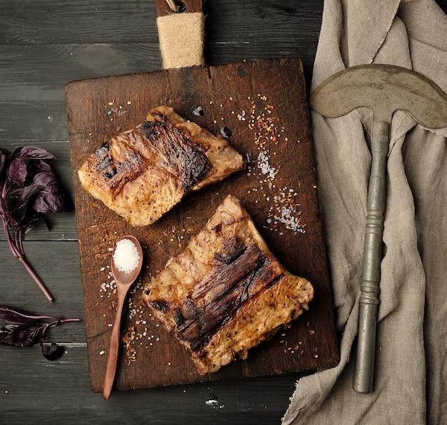 Côtes de porc grillées sur une planche à découper en bois marron
