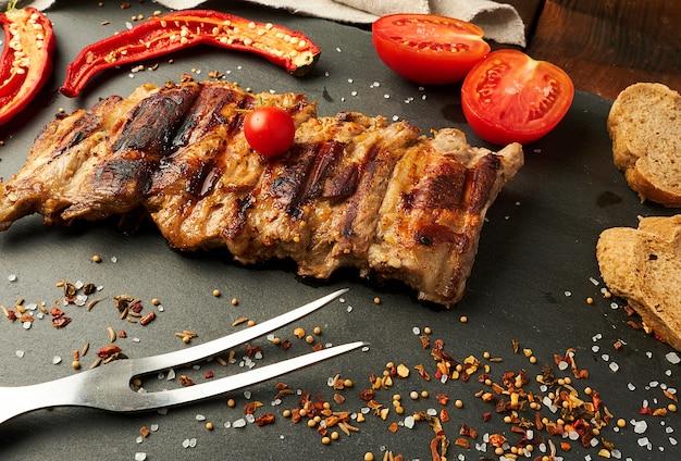 Côtes de porc grillées sur un tableau noir, tomates rouges fraîches
