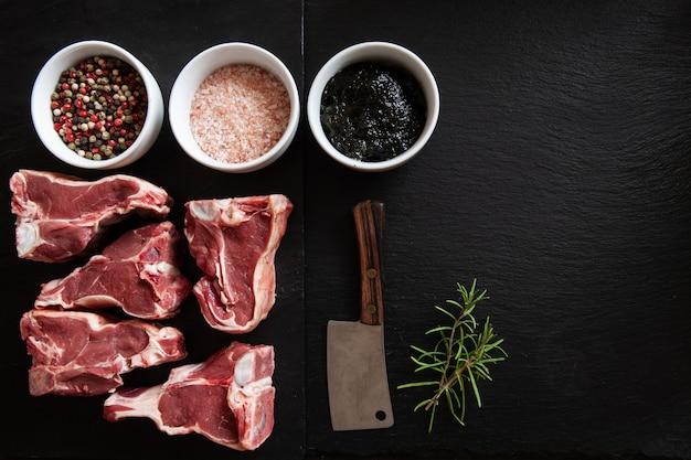 Côtes de viande d'agneau fraîches crues, gelée de menthe anglaise traditionnelle et assaisonnements sur pierre noire