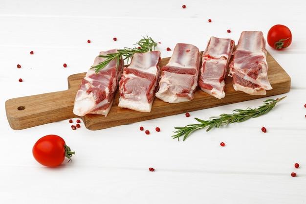 Côtes de viande crue sur planche de bois sur fond blanc