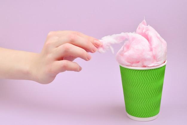 Coton bonbon rose vif dans une tasse en plastique dans une main de femme sur fond lilas.