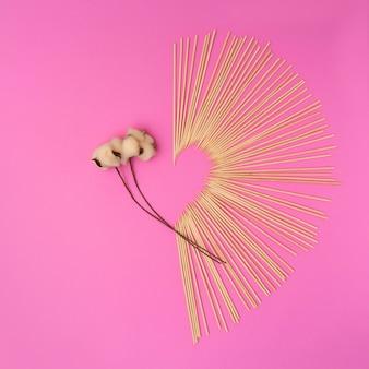 Coton doux et coeur de la saint-valentin composé de minuscules bâtons de bois sur fond rose vif. composition à plat minimale.