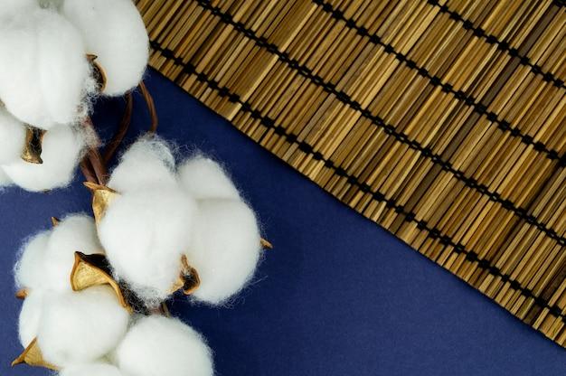 Coton naturel sur la table avec des feuilles. contexte de votre objet