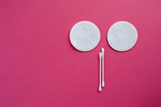 Des cotons-tiges et des disques isolés sur un fond rose. produits d'hygiène.
