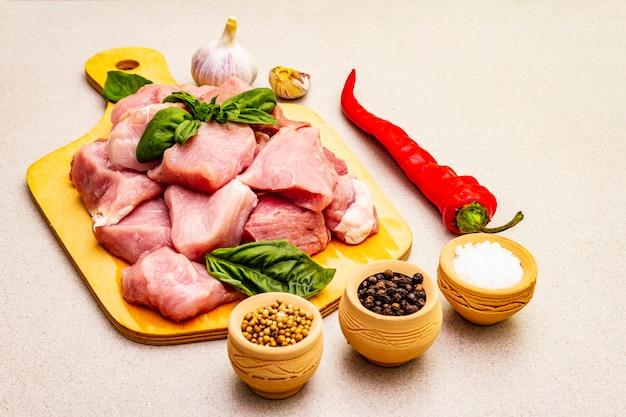 Cou de porc cru, coupé en morceaux avec des légumes frais et des épices sèches