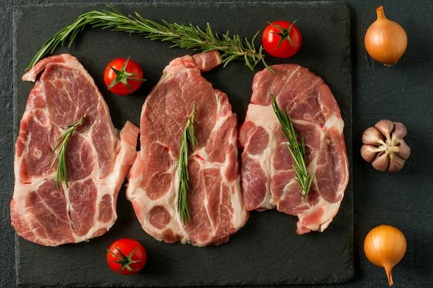Cou de porc cru frais biologique alimentaire sur pierre d'ardoise noire avec romarin, oignon et tomates.