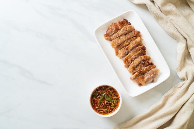 Cou de porc grillé ou cou de porc bouilli au charbon de bois avec trempette épicée thaïlandaise