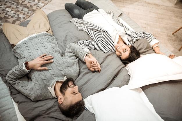 Couché ensemble. enthousiaste homme riant en pull gris, profitant du temps avec sa femme tout en lui tenant la main